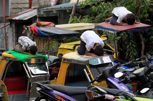 Muslim youths pray atop auto-rickshaws in front of al-Satie mosque in Manila, Philippines.