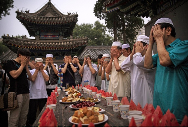 Chinese Muslims of the Hui ethnic minority pray over food before breaking their fast at the historic Niujie mosque on July 3.