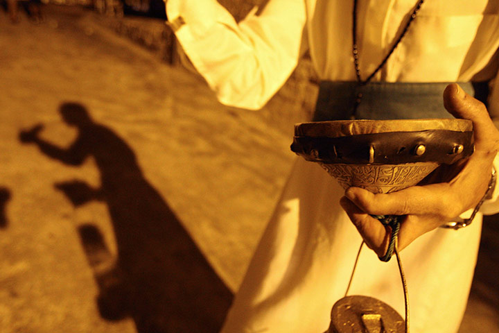 A musaharati (dawn awakener) strikes his drum to wake Muslims for their sahur (last meal) before the day's fast in Sidon, Lebanon.