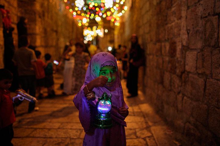 A young Palestinian girl holds a traditional Ramadan lantern in Jerusalem.