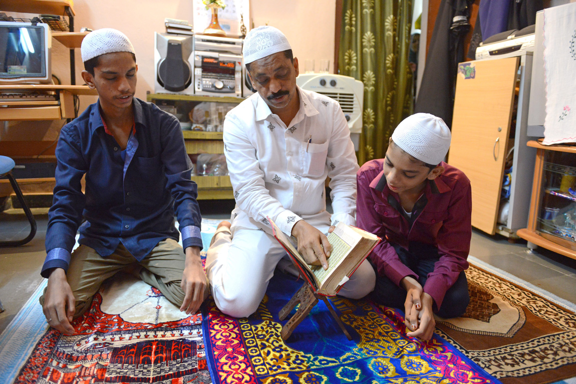 An Indian Muslim family reads the Quran after breaking their fast at their home in Hyderabad, India.