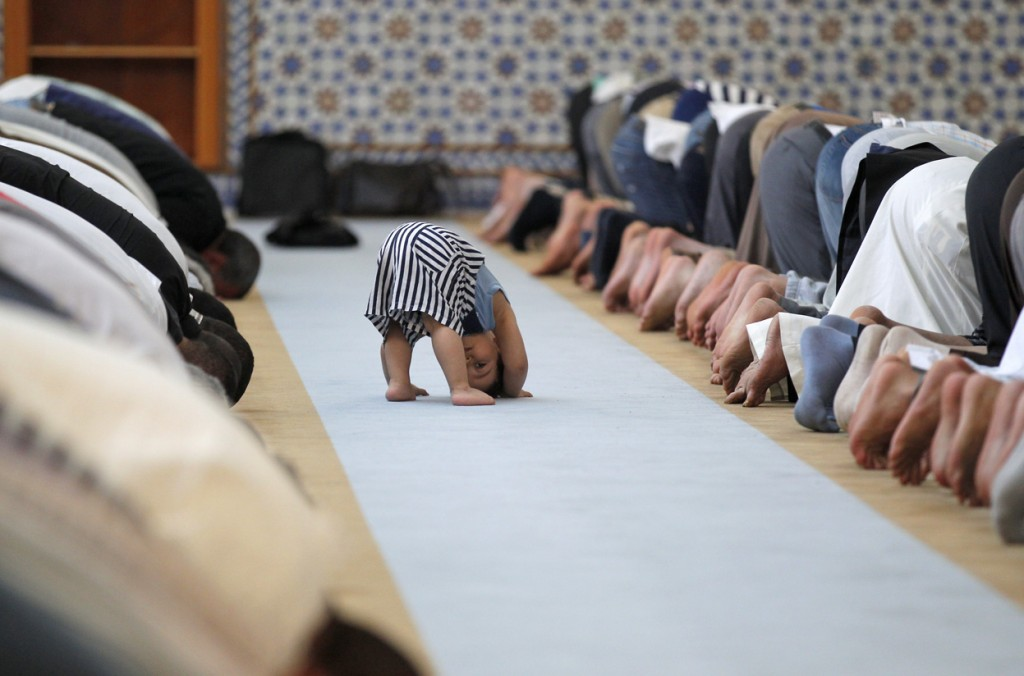 A child leans down near members of the Muslim community attending midday prayers at Strasbourg Grand Mosque in Strasbourg, France, on the first day of Ramadan.