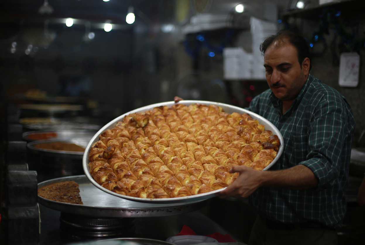 A pastry chef holds a tray of Arabic sweets at his bakery in Gaza City on the eve of the start of Ramadan, on July 9, 2013.