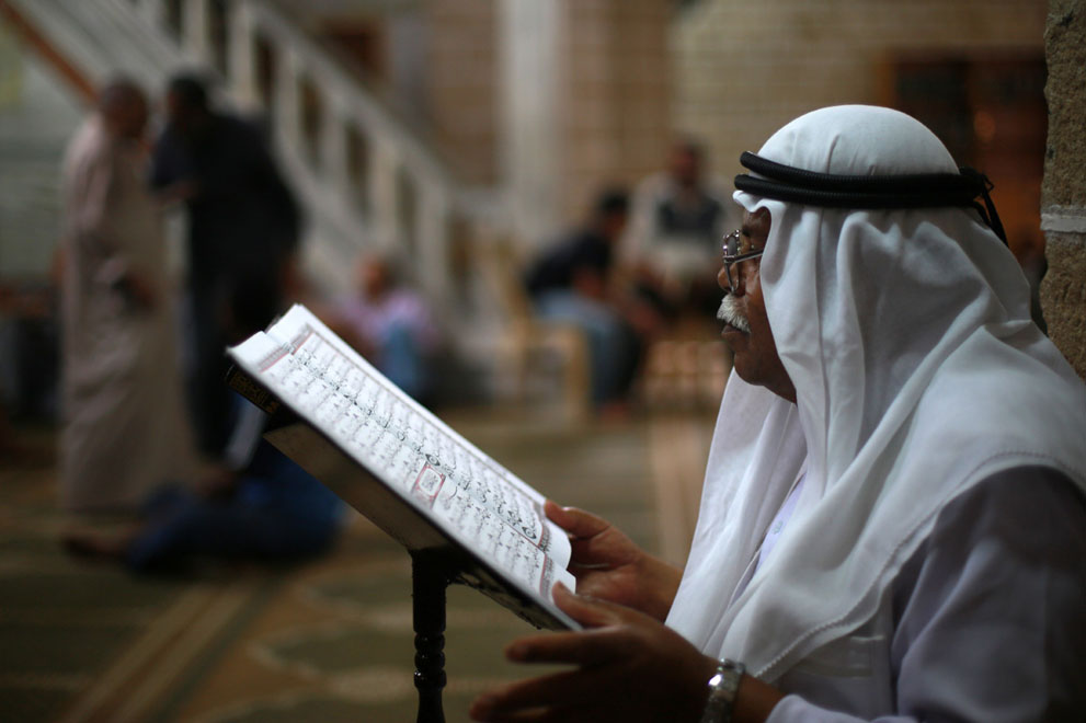 A Palestinian man reads verses from the Quran, Islam's holy book, at al-Omari mosque on the first day of Ramadan.
