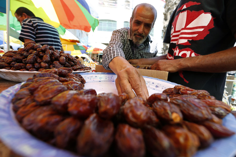 A Palestinian arranges dates for sale on the first day of Ramadan in a market in the West Bank city of Ramallah.