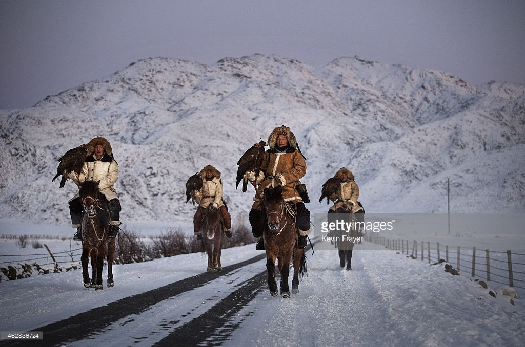 XINJIANG, CHINA - JANUARY 29:  Chinese Kazakh eagle hunters from the Beysenbay family who are all brothers ride together with their eagles before a local competition on January 29, 2015 in the mountains of Qinghe County, Xinjiang, northwestern China.