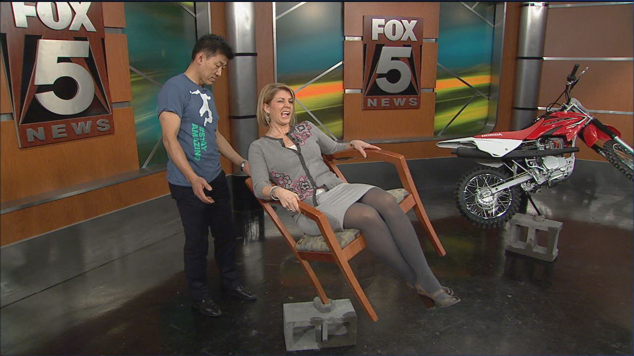 Byun balances Fox 5's Melanie Alnwick while she sits on a chair.