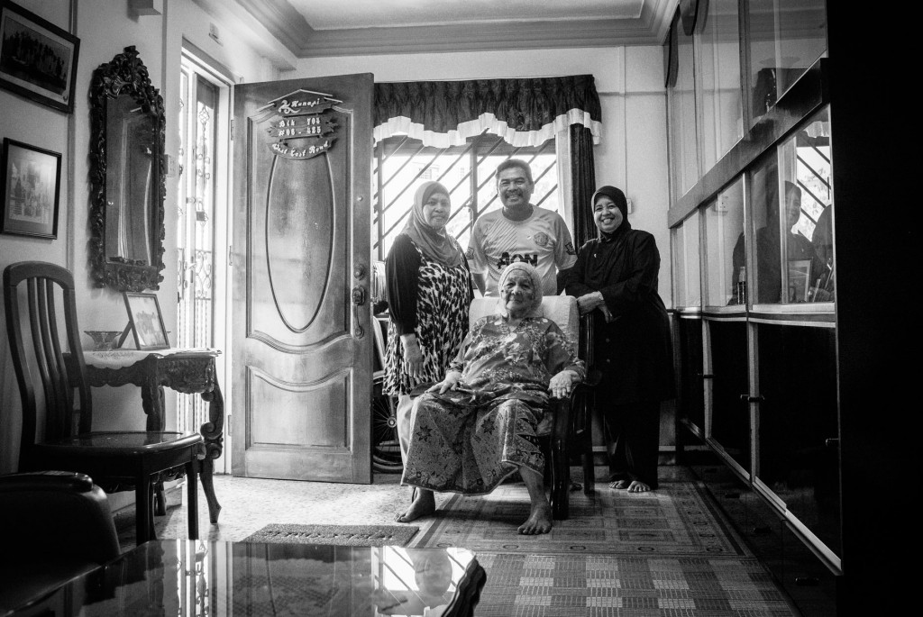 Pulau Seking Penghulu's wife Saniah Bte Ali with her children Rahimah and Kamal, and his wife. Since their resettlement from the island in 1994, they've called this West Coast flat their home.