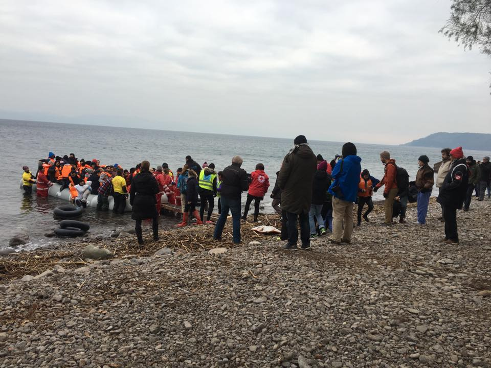 Volunteers welcoming refugees who have arrived in boats to Lesbos